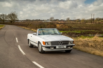 Rear side view of a white SL Shop Mercedes-Benz R107 300 SL hire car