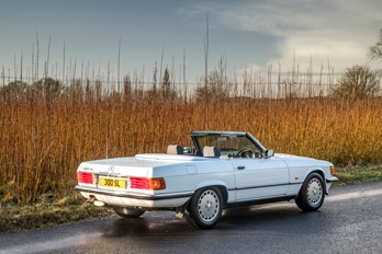 Front side view of a white SL Shop Mercedes-Benz R107 300 SL hire car