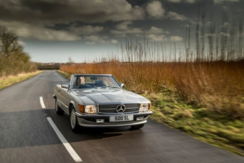 Rear side view of a white SL Shop Mercedes-Benz R107 500 SL  hire car
