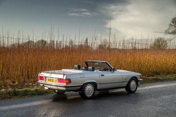 A man driving a white SL Shop Mercedes-Benz R107 500 SL  hire car along a country road