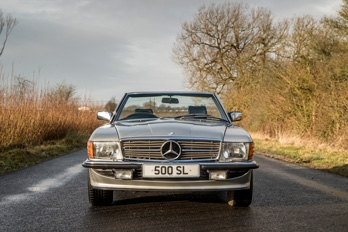 Front side view of a white SL Shop Mercedes-Benz R107 500 SL  hire car