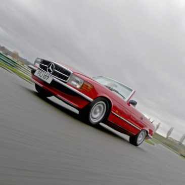 A red SL Shop Mercedes-Benz R107 SL on a race track