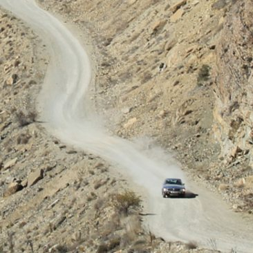 An SL Shop Mercedes-Benz 107 driving down a dusty mountain track