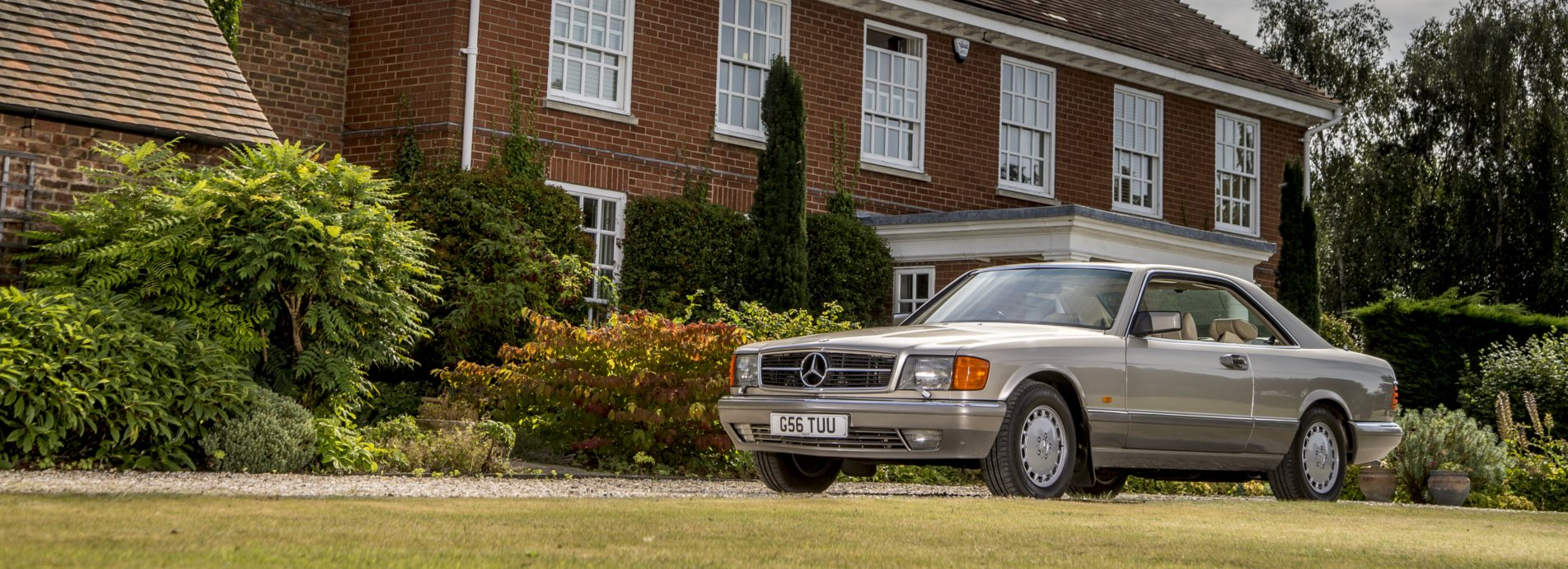 A gold SL Shop Mercedes-Benz R129 parked in front of a house