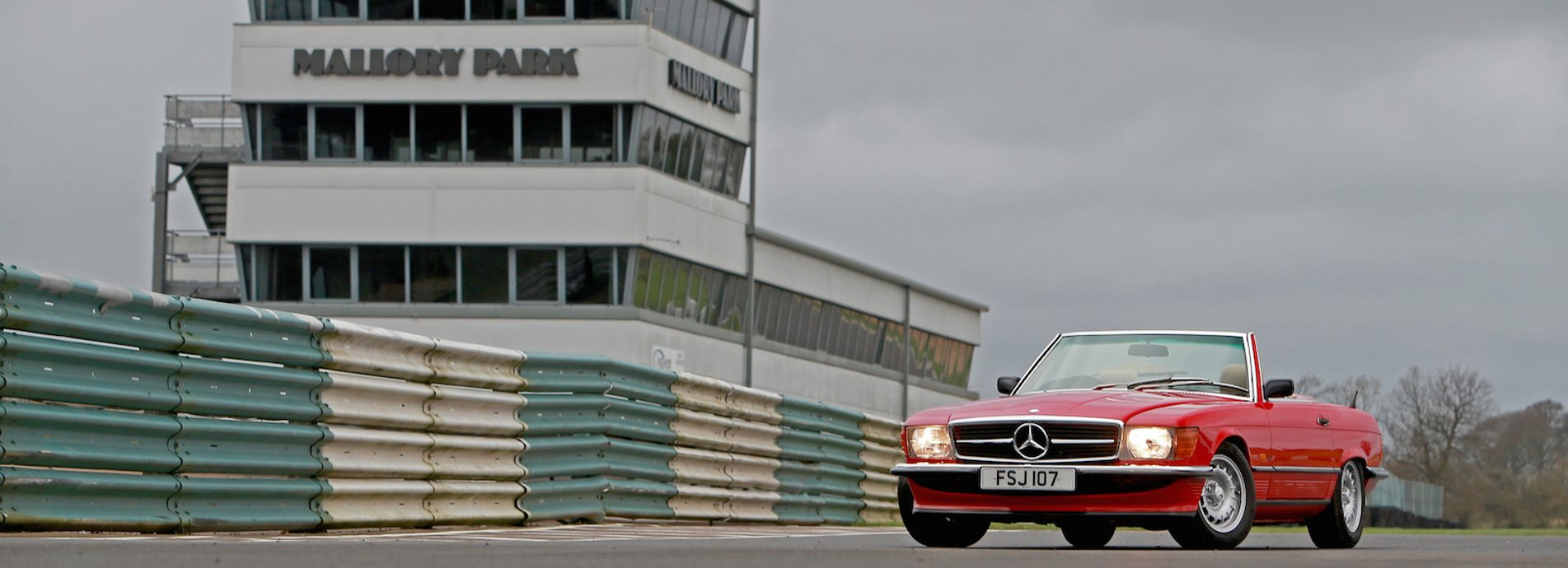 A red SL Shop Mercedes-Benz R107 SL SportLine parked on a race track
