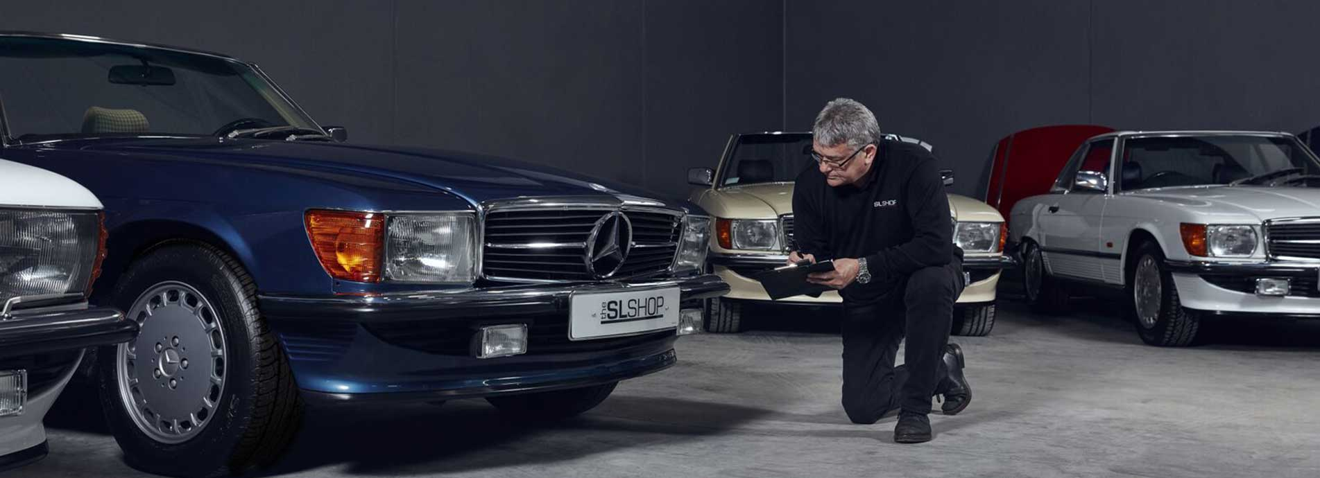 Man inspects a Mercedes-Benz R107 SL stored at The SL Shop