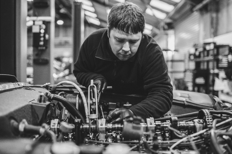 Man examining car engine during W113 Servicing.