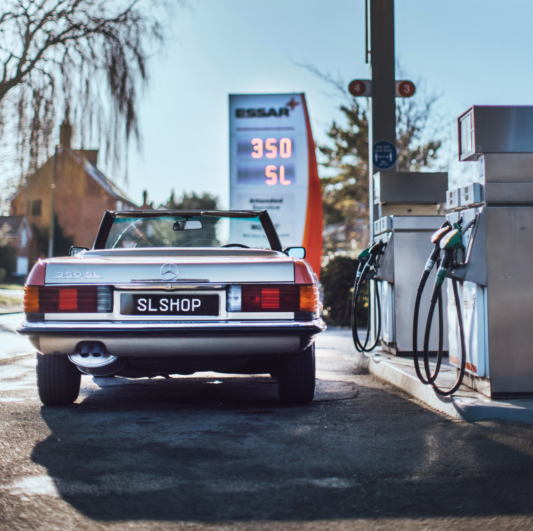 SLSHOP's 1971 Mercedes R107 350 SL standing proud a classic-style petrol station in the UK.